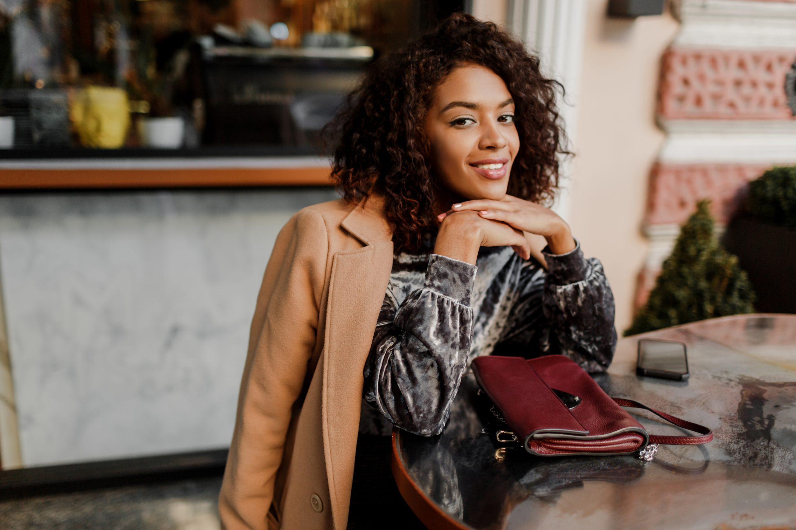 Outdoor  portrait of  beautiful  smiling black woman with stylish afro hairs sitting in cafe in Paris. Wearing trendy velvet dress and beige coat. Luxury bag.