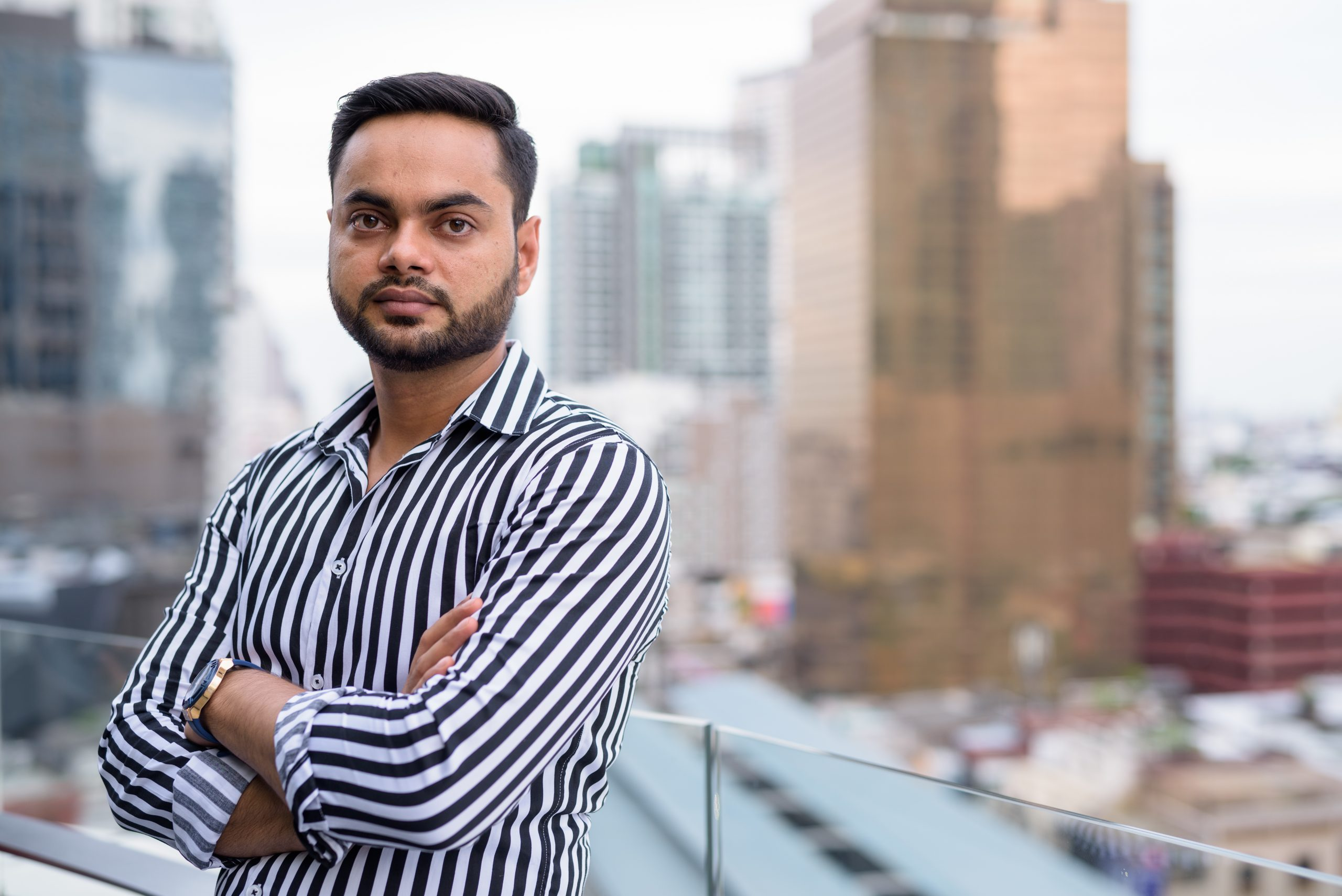 Portrait of young bearded Indian businessman against view of Bangkok city